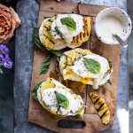 Grilled Pineapple Caprese Eggs Benedict with Coconut-Almond Hollandaise.