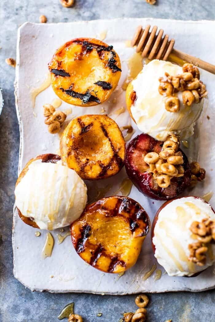 overhead photo of Cinnamon Grilled Peaches with Mascarpone Ice Cream on plate with honey drizzler