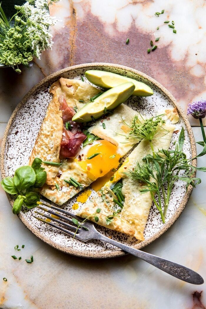 overhead photo of cut into Baked Egg Crepes with Spring Herbs and Avocado