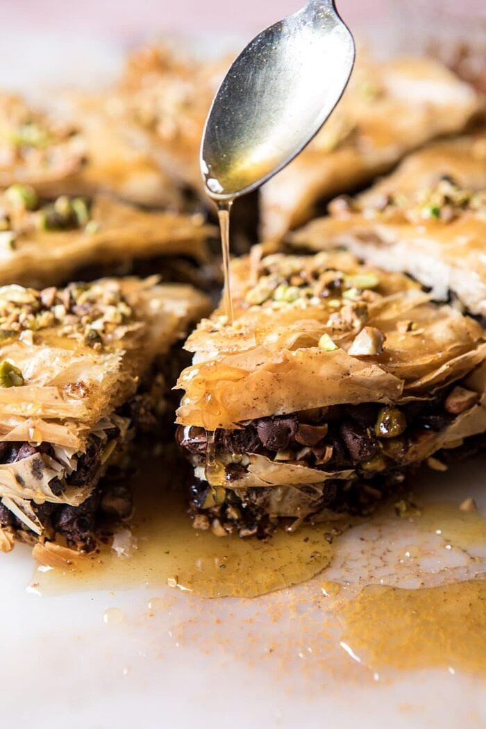 drizzling honey over Easy Pistachio Chocolate Baklava, close up photo