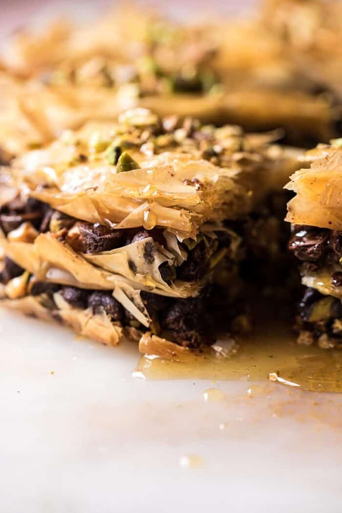 side angle photo of Easy Pistachio Chocolate Baklava with honey dripping down