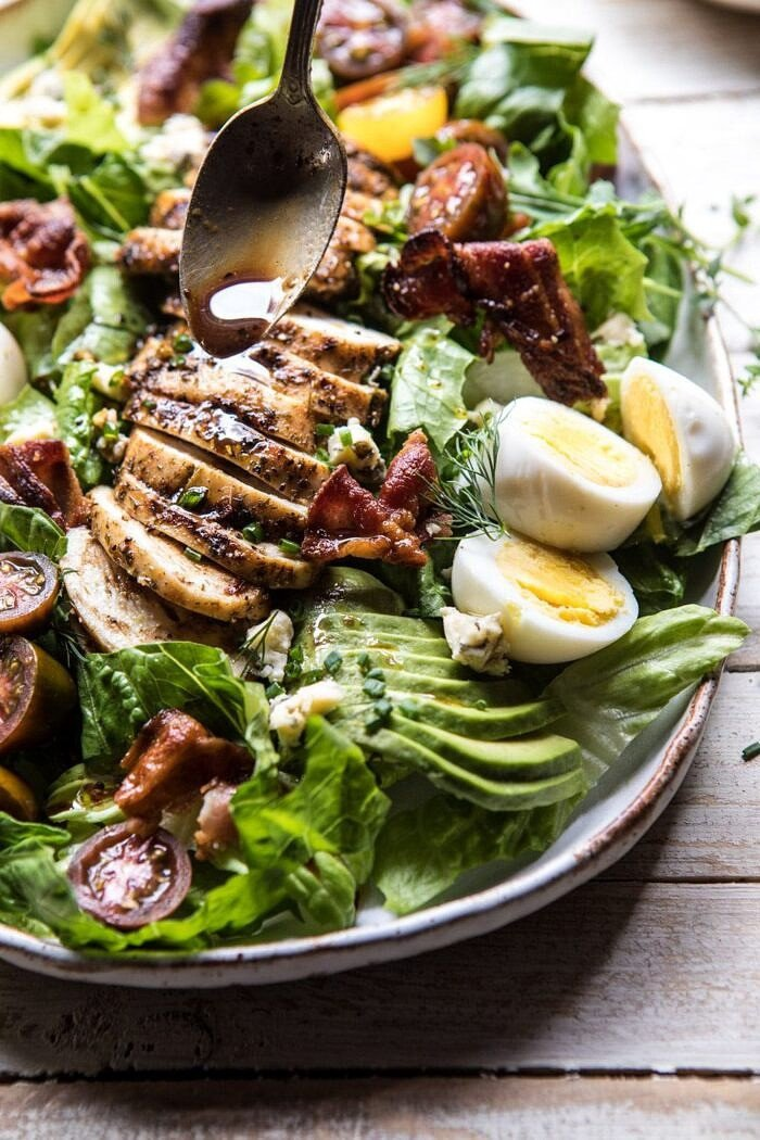 side angled photo Balsamic Grilled Chicken Cobb Salad with spoon and dressing