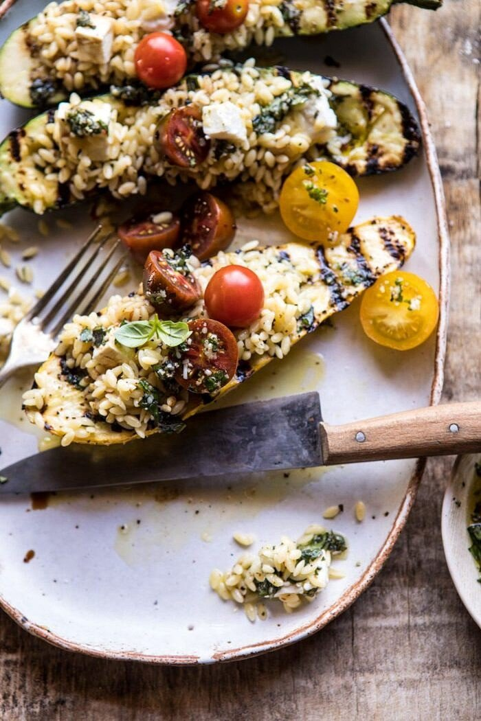 cute into photo of Grilled Pesto Zucchini Stuffed with Tomatoes and Orzo