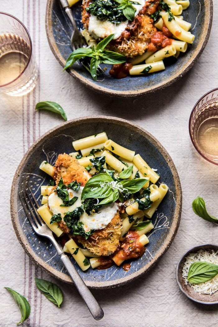 overhead photo of Spring Chicken Parmesan with Tuscan Kale Pesto with wine glasses