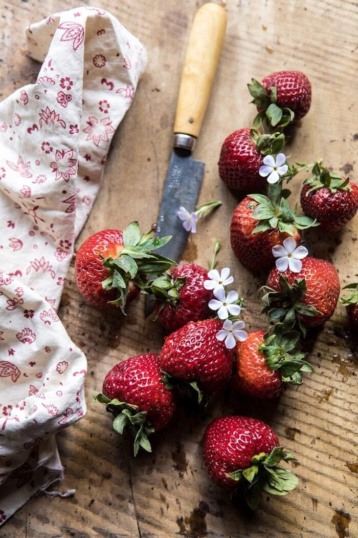overhead photo of strawberries with flowers and pairing knife