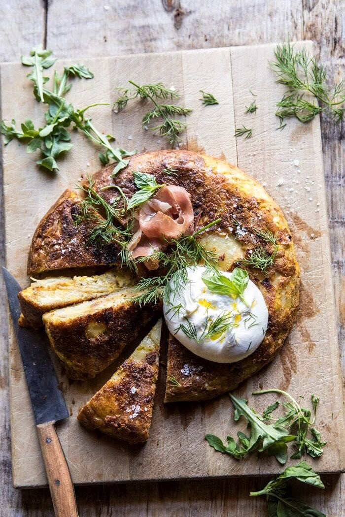 overhead photo of Spanish Tortilla with Burrata and Herbs with knife in photo