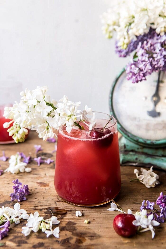angled photo of Hibiscus Cherry Vodka Spritz with lilacs and cherries