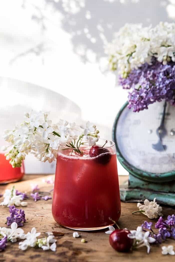 front on, far back photo of Hibiscus Cherry Vodka Spritz with lilacs