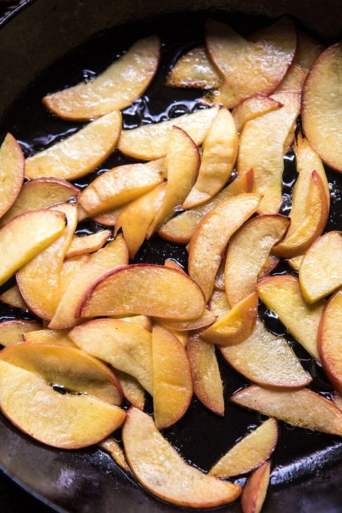 overhead photo of sliced peaches in browned butter in skillet