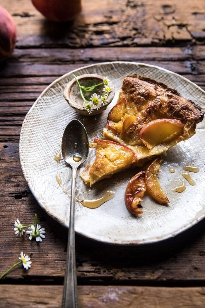 Browned Butter Cinnamon Peach Dutch Baby on a plate with spoon and flowers