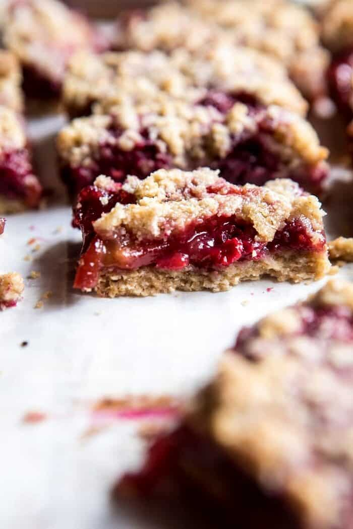 close up photo of Buttery Raspberry Crumble Bar broken in half to show the filling