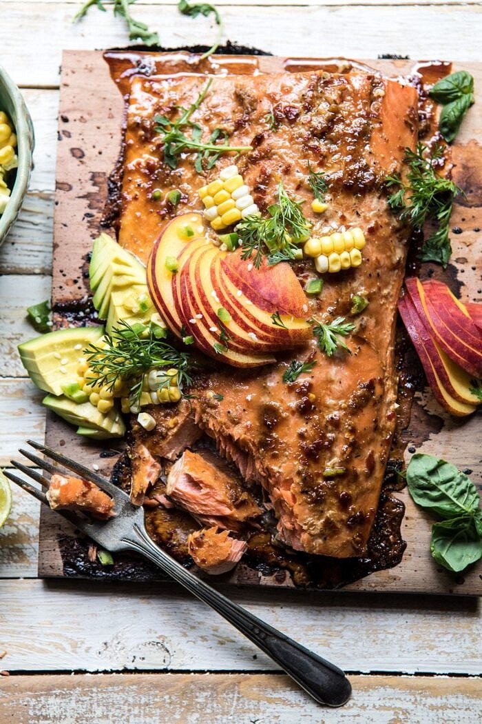 overhead photo of Honey Ginger Cedar Plank Grilled Salmon with Avocado Salsa and fork in photo with salmon