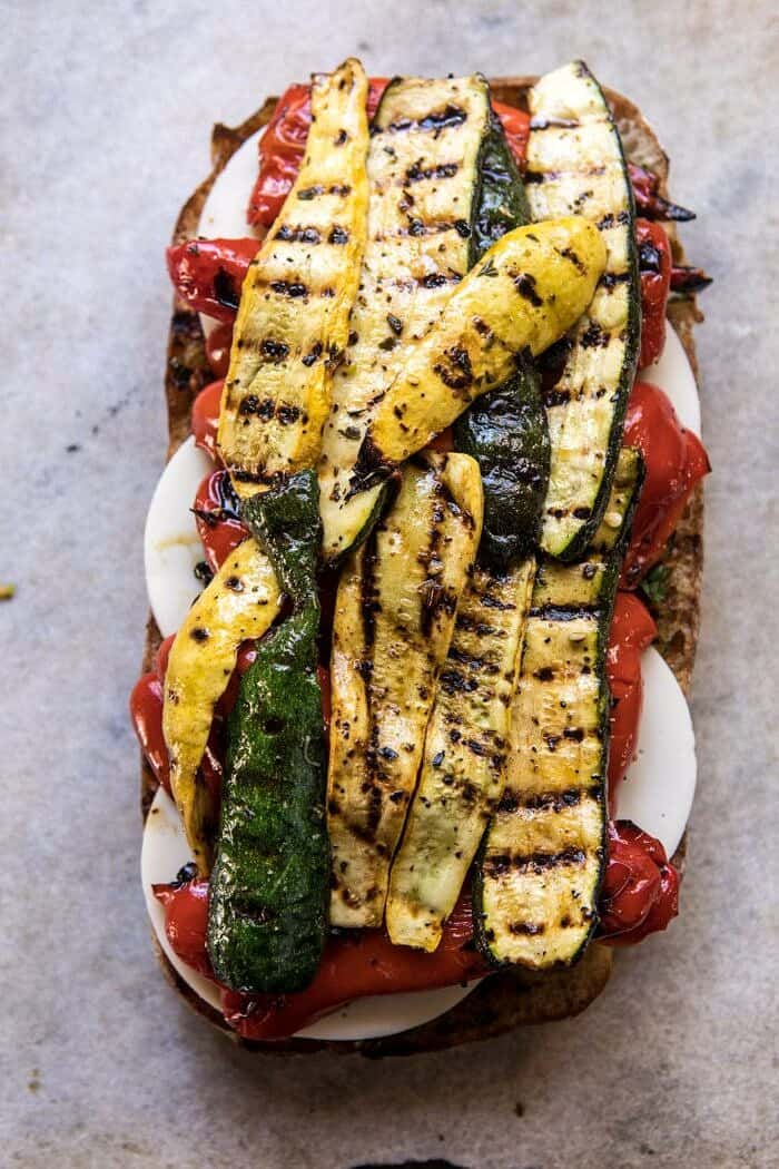overhead photo of Marinated Veggie Cheese Sandwich with Sun-Dried Tomato Pesto and grilled zucchini on top