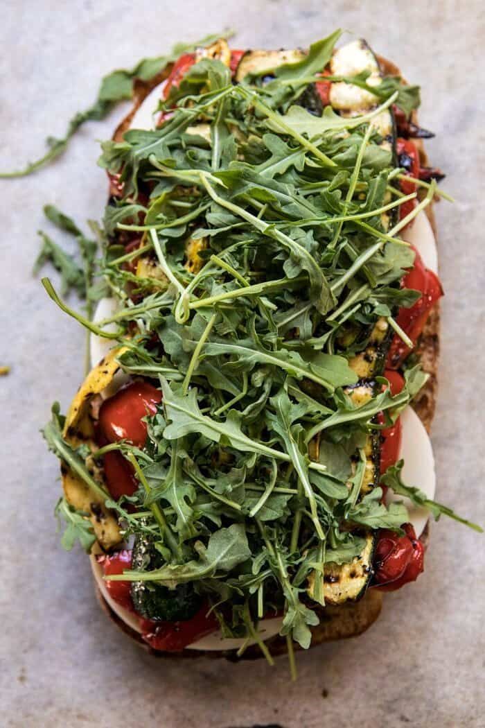 overhead photo of Marinated Veggie Cheese Sandwich with Sun-Dried Tomato Pesto and arugula on top