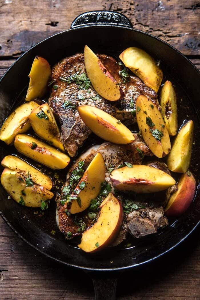 overhead photo of Skillet Balsamic Peach Pork Chops with raw peaches in skillet
