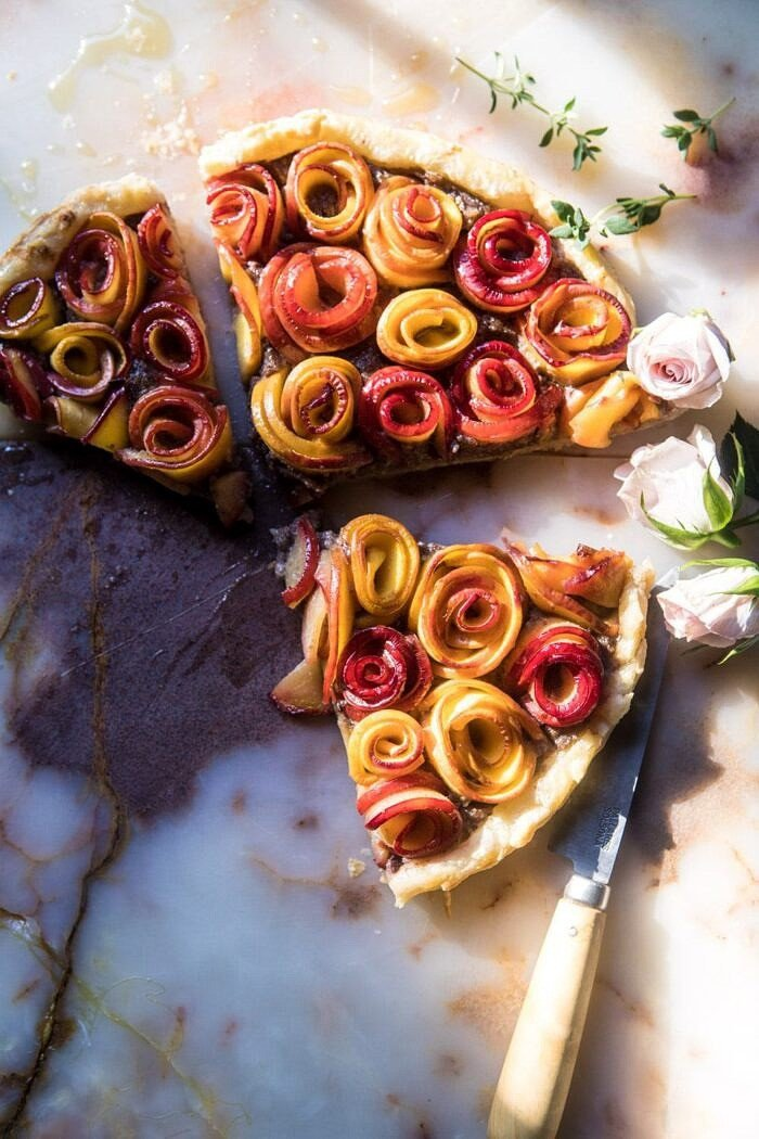 overhead photo of Sweet Peach Rose Tart cut into 3 triangles with sun streaking through