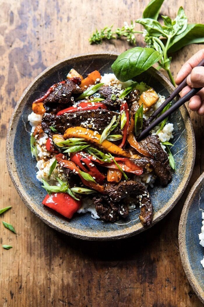 overhead photo of 30 Minute Korean Beef and Peppers with Sesame Rice with hands in photo