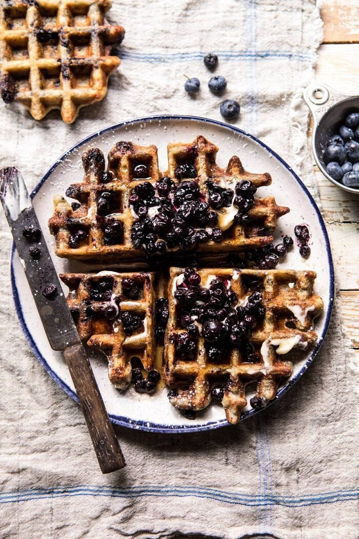 overhead photo of Bursting Blueberry Cornmeal Waffles with butter knife and fresh blueberries in photo