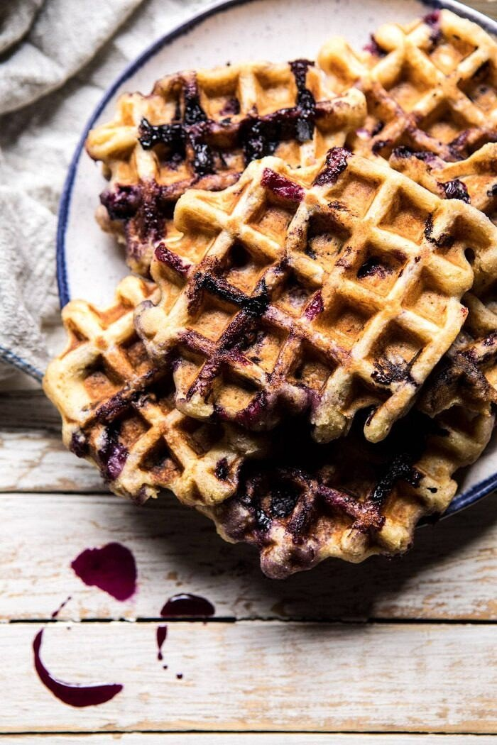 Bursting Blueberry Cornmeal Waffles with syrup and on a plate