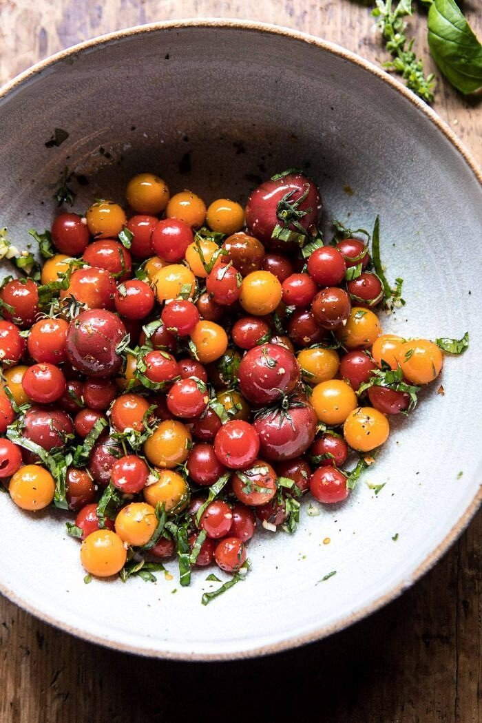 overhead photo of raw tomatoes with garlic and herbs