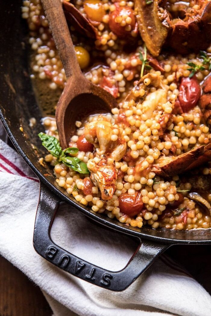 overhead close up photo of One Pot Tomato Basil Lobster and Herbed Pearl Couscous with wooden spoon