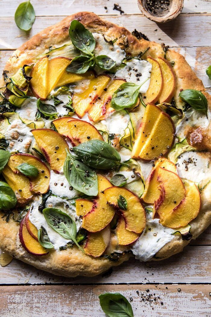 overhead photo of Pesto Zucchini and Peach Pizza with Burrata with sunlight on pizza
