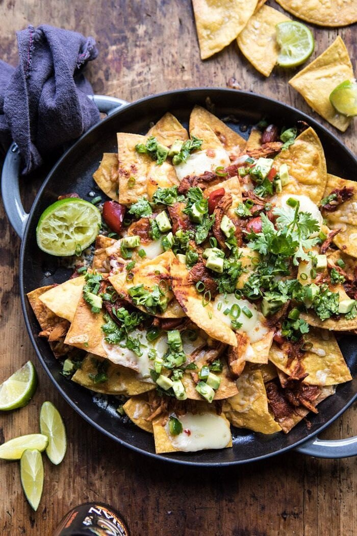 overhead photo of Chipotle Braised Chicken Nachos on plate with beer in photo