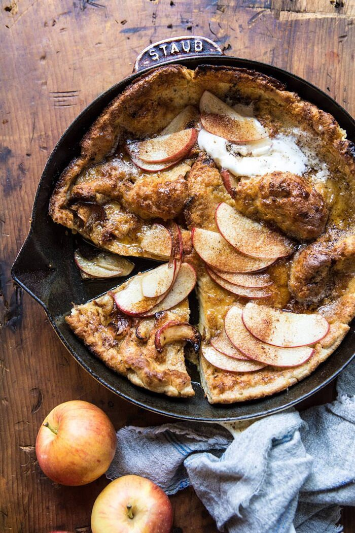 overhead photo of Cinnamon Apple Puffed Pancake in skillet with pieces cut out