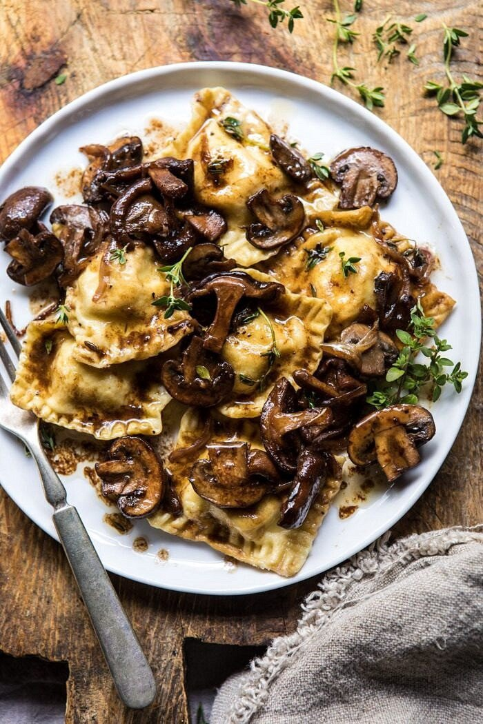 overhead, close up photo of Herby Buttered Balsamic Mushroom Ravioli on plate with fork
