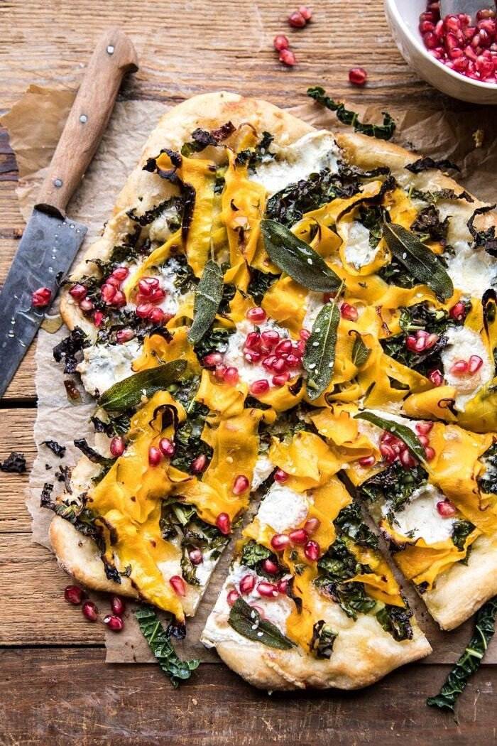 overhead photo of Caramelized Onion, Butternut Squash, and Crispy Kale Pizza with piece cute out