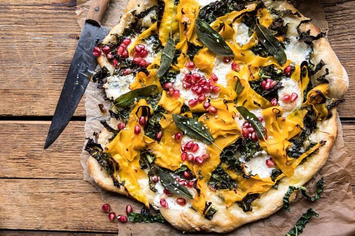 horizontal photo of Caramelized Onion, Butternut Squash, and Crispy Kale Pizza with knife in photo
