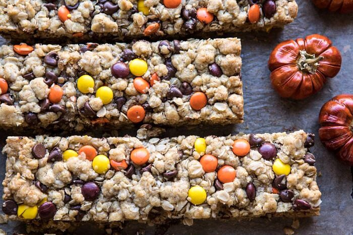 horizontal photo of Monster Oatmeal Chocolate Chip Cookie Bars with mini pumpkins in photo