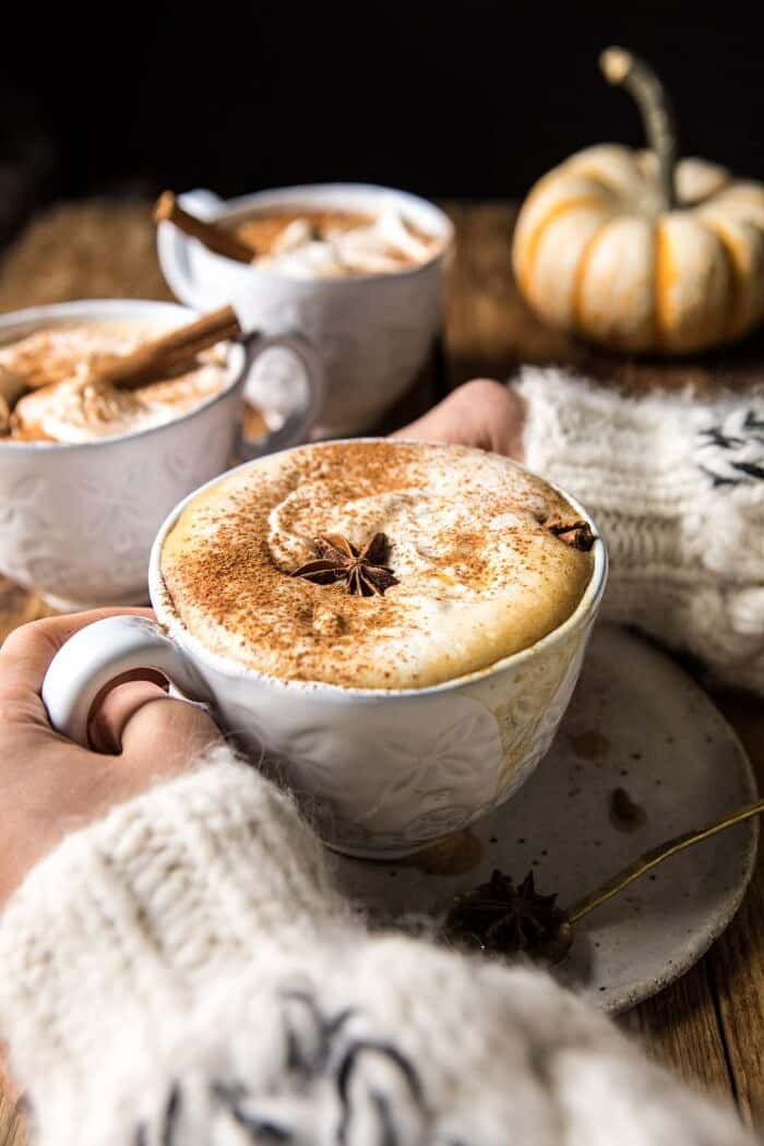 Spiced Pumpkin Maple Latte with hands on mug and 3 mugs in photo