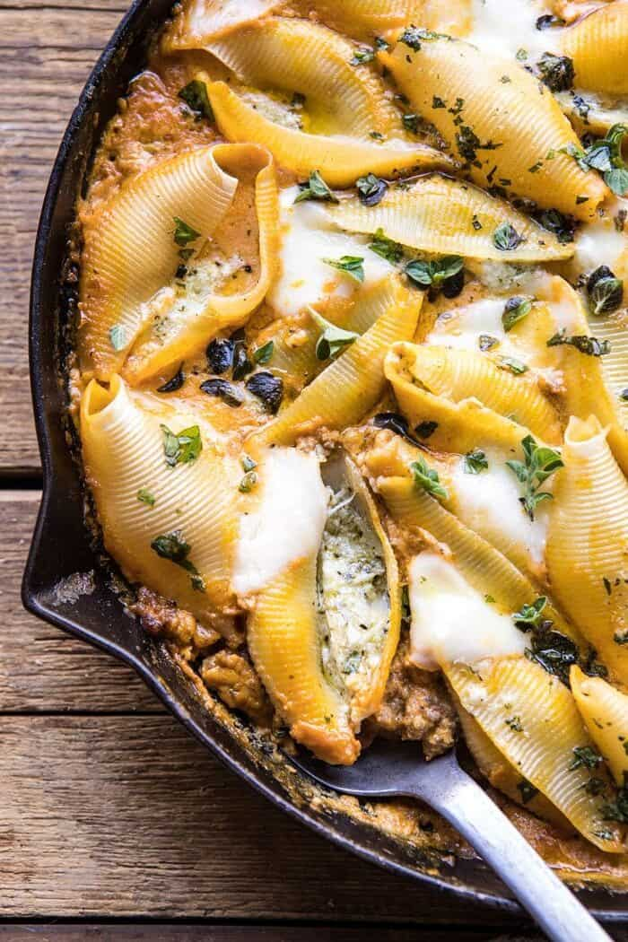 close up photo Spicy Pumpkin and Pesto Cheese Stuffed Shells with spoon in skillet