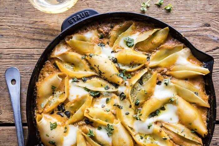 horizontal photo of Spicy Pumpkin and Pesto Cheese Stuffed Shells in skillet