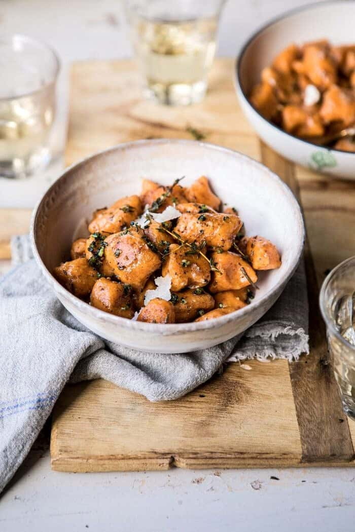 Sweet Potato Gnocchi with Herbed White Wine Pan Sauce in bowls with wine glasses and towel in photo