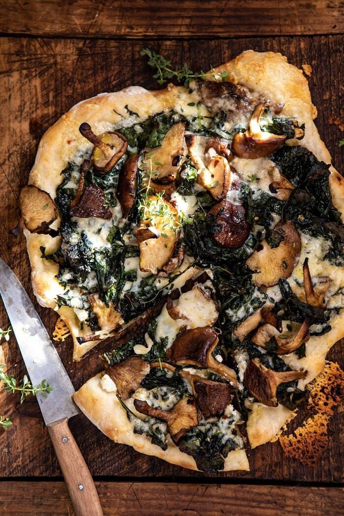 overhead photo of Roasted Mushroom Kale Pizza with slice cut and knife on board