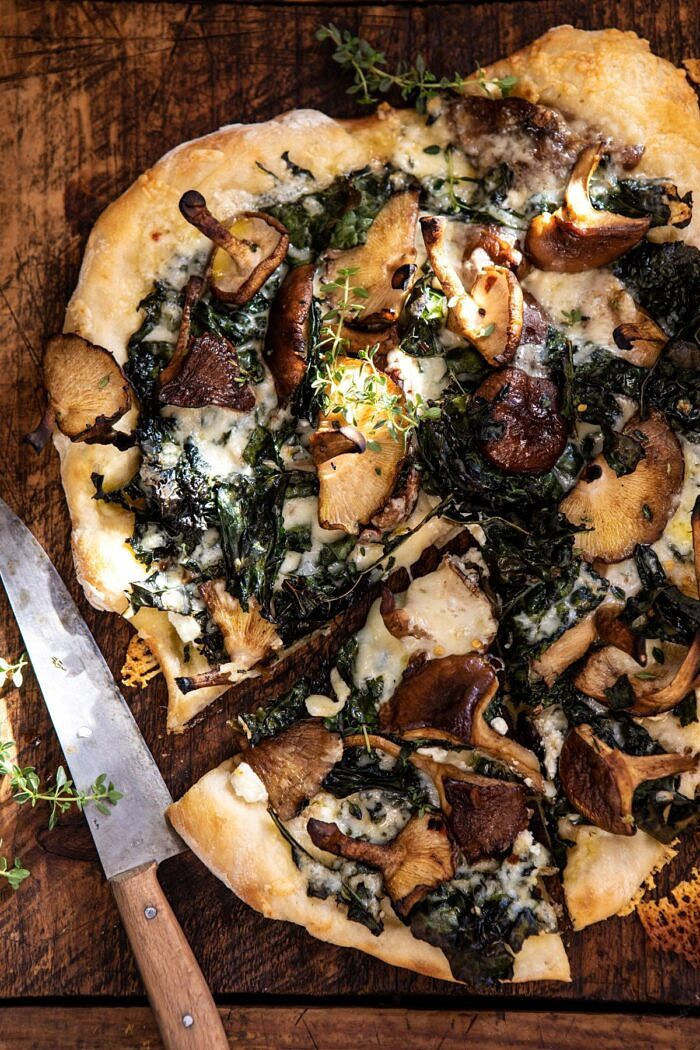 overhead close up photo of Roasted Mushroom Kale Pizza with slice cut and knife in photo