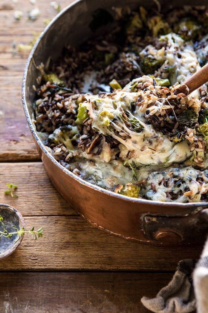 side angle photo of One Pan Broccoli Cheese Wild Rice Casserole with spoon scooping rice out of pan
