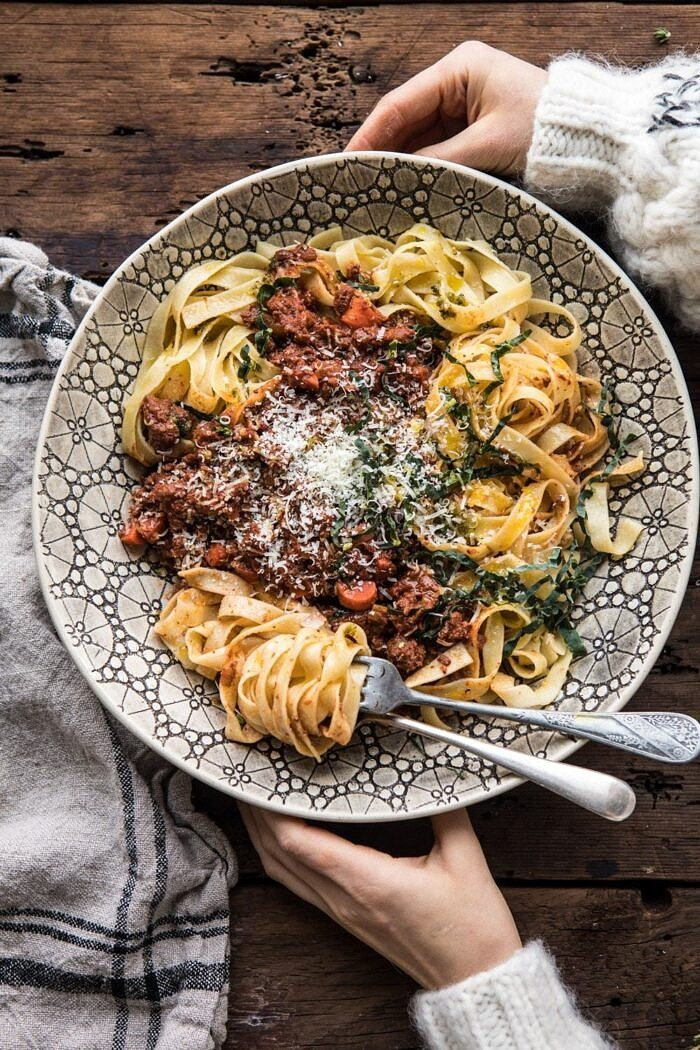 overhead photo of Slow Cooker Vodka Bolognese Pasta with hands on bowl