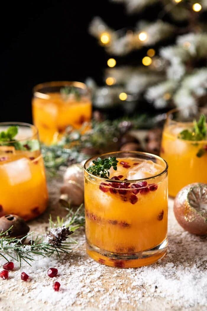 3/4 angled photo of Holy Jolly Christmas Citrus Cocktail with tree in background