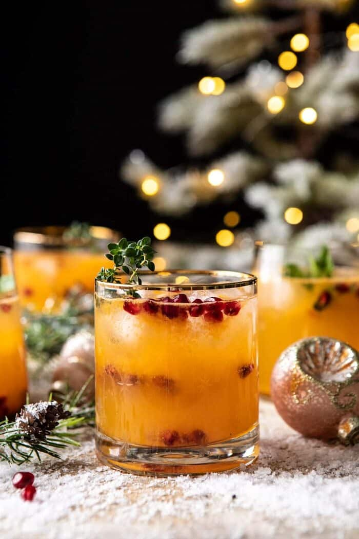 side angle close up photo of Holy Jolly Christmas Citrus Cocktail with tree in background
