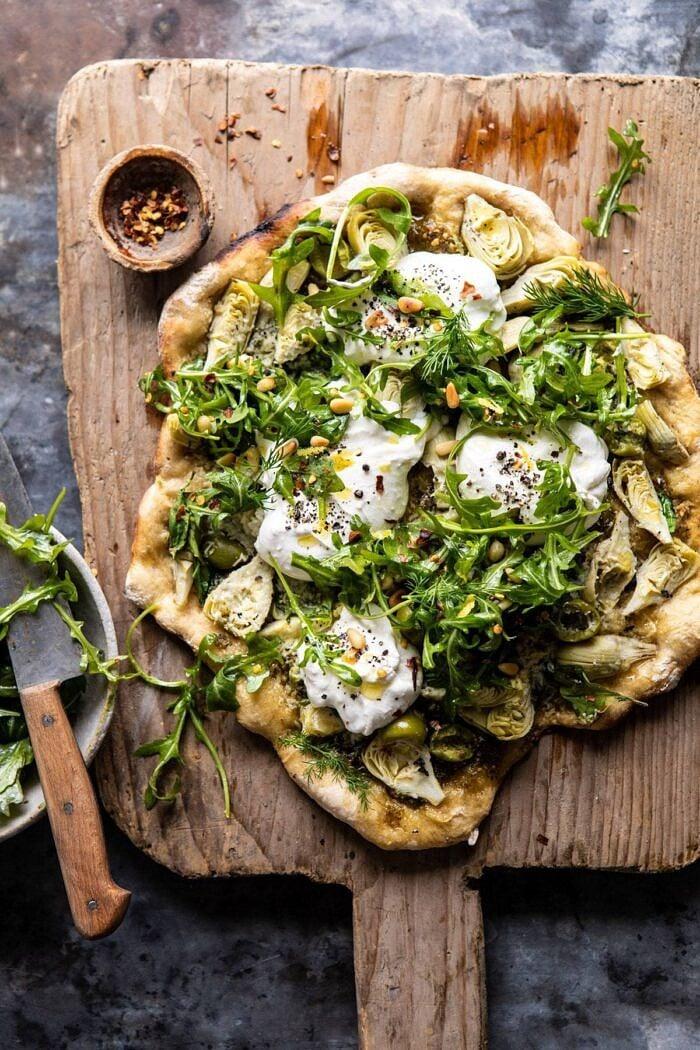 Artichoke Pesto and Burrata Pizza with Lemony Arugula before being cut