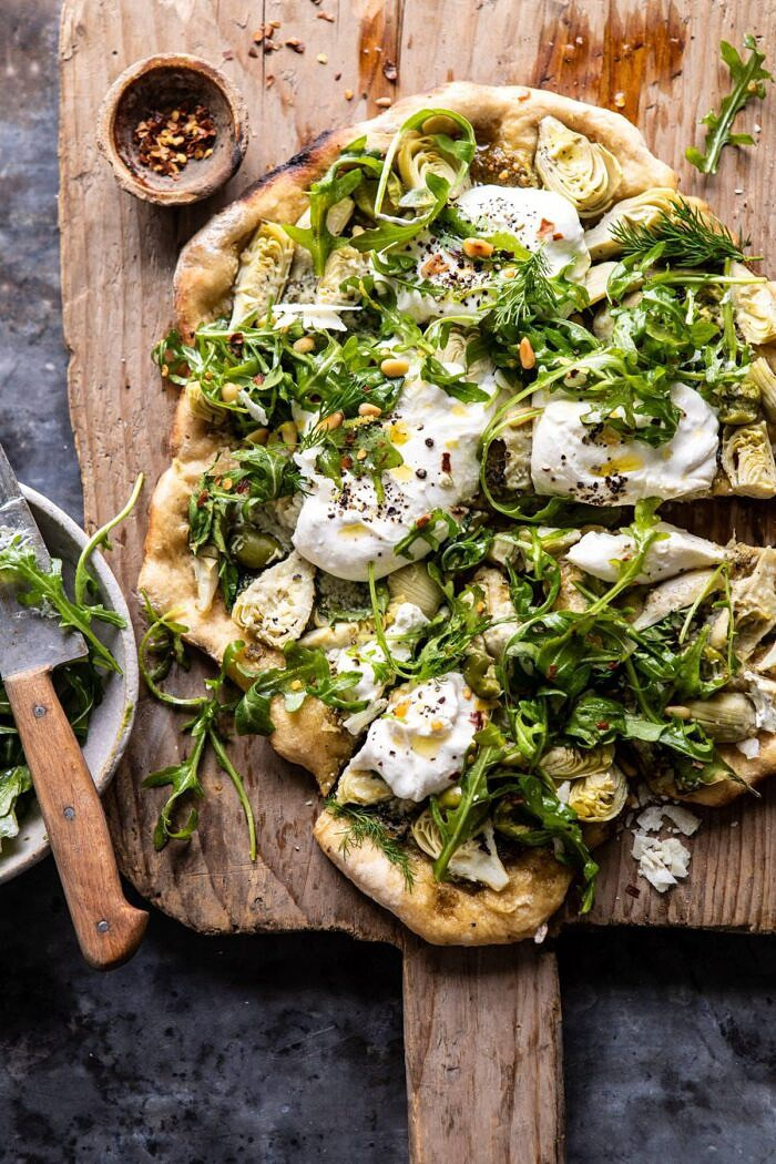 overhead photo of Artichoke Pesto and Burrata Pizza with Lemony Arugula after being cut