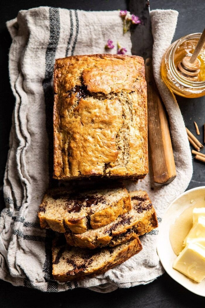 over head photo of sliced Chocolate Chunk Coconut Banana Bread with honey jar and butter on table