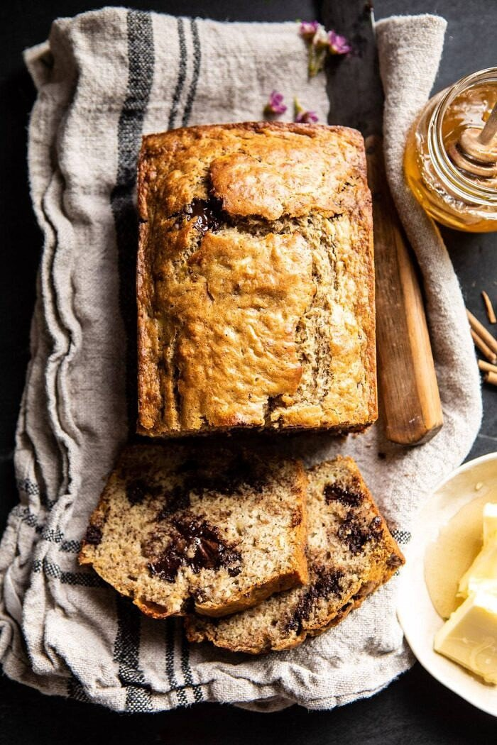 Chocolate Chunk Coconut Banana Bread with 2 pieces cut and honey in photo