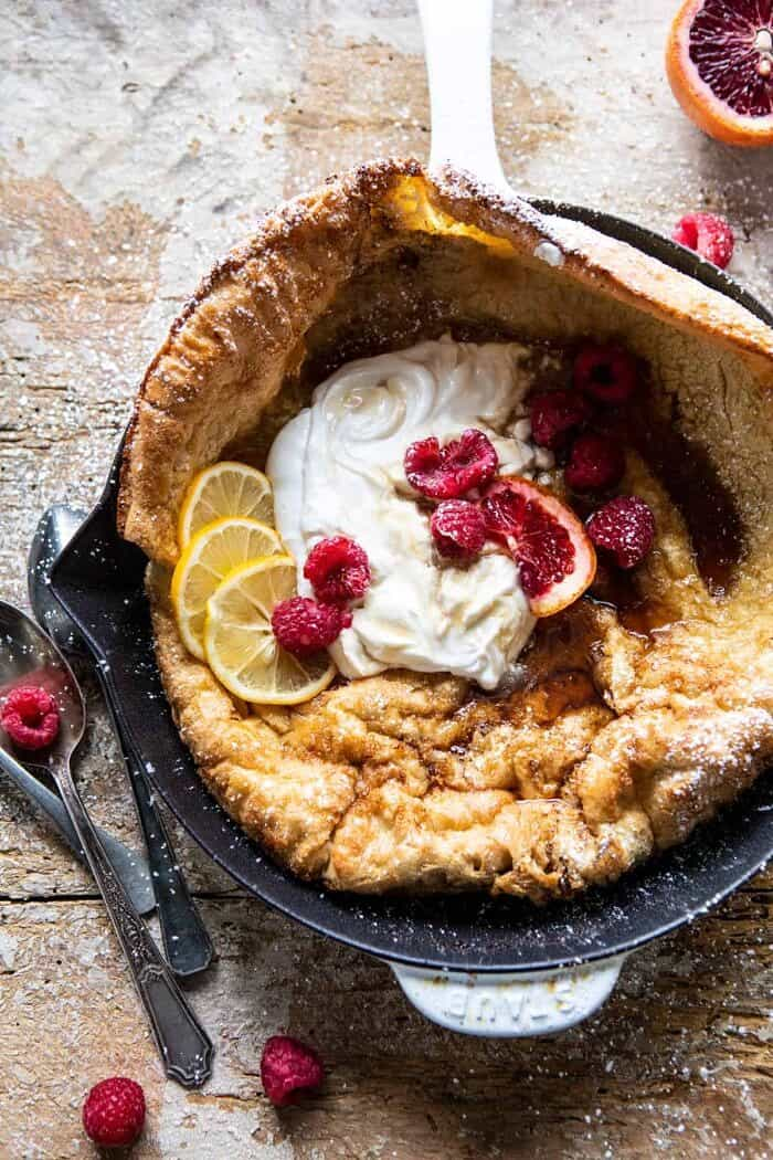 overhead close up photo of Whole Wheat Dutch Baby in skillet with Meyer Lemon Whipped Ricotta and berries
