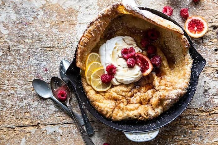 overhead photo of Whole Wheat Dutch Baby with Meyer Lemon Whipped Ricotta with berries and spoon on surface