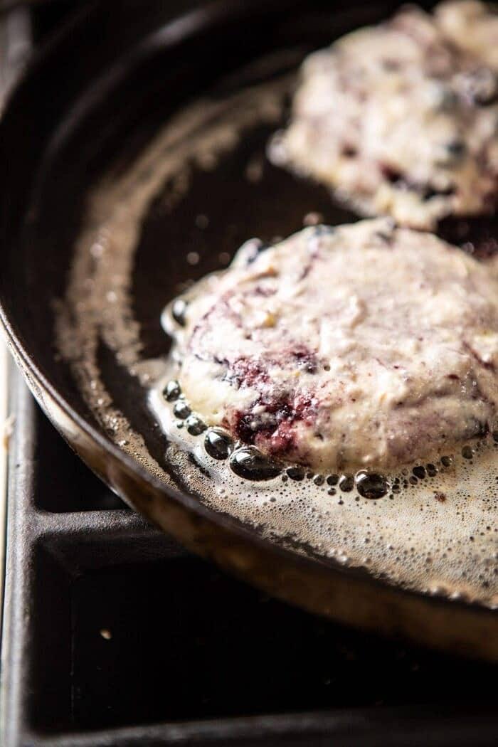 Blueberry Lemon Ricotta Pancakes on skillet cooking