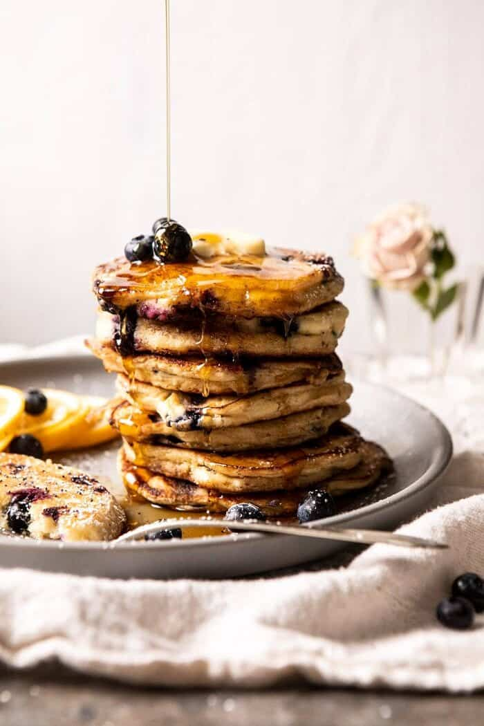 close up side angled photo of Blueberry Lemon Ricotta Pancakes with syrup being drizzled on